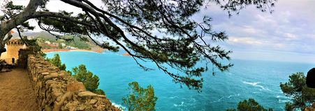 Sea, medieval wall, trees and landscape in Tossa de Mar, Spain royalty free stock photos