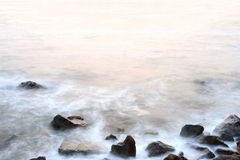 Sea mist softness of the tides and sunset at evening with rocks Stock Image