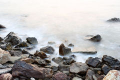 Sea mist softness of the tides and sunset at evening with rocks Stock Photo