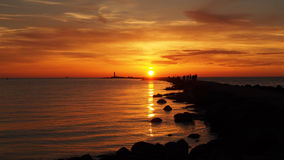 Orange sunset and sea coast. Sea moll at orange sunset stock photos