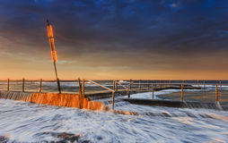 Sea Mona Vale Light Pole Pool. High rise surfing waver flowing over the rock pool at Mona Vale beach in Sydney. Pool fence and sign pole in warm rising sun light Royalty Free Stock Photos