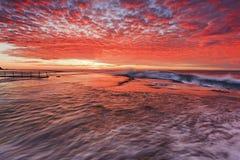 Sea Mona vale pink flat stream. Red colourful sunrise over sea horizon at Mona Vale beach of Sydney northern beaches around rock pool Stock Photos