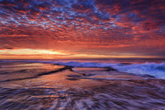 Sea mona vale pink sun over rockbed Royalty Free Stock Photo