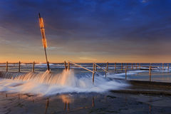 Sea Mona Vale Pool Over sunlight. Mona vale rock  pool entrance steps and wire fence under overflowing ocean wave surfing through at sunrise with warm sun  light Stock Image