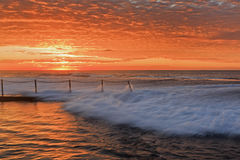 Sea Mona Vale Pool Wave Orange. Mona Vale beach rock pool at sunrise. Saturated red sun lights stormy surfing waves of high tide ocean Stock Images