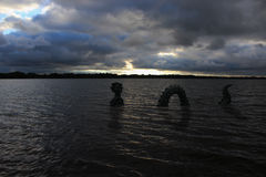 Sea monster in Medicine Lake. A sea monster surfaces along the shore of Medicine Lake close to sunset under dark clouds stock image