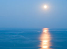 Sea and moon. View of the sea with the moon in the sky, reflecting on the surface of the water Stock Image