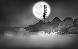 Sea Moon. Waves splashing at night around jagged rocks, illuminated by a large white moon. An arial mast is silhouetted in front of the moon Royalty Free Stock Photography