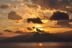 Orange Sunset seen from my window on the and of the day. On the sea with mountain in the back sun is going to sleep and saying goodnight with beautiful colors Royalty Free Stock Photography