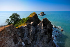 Sea mountain cliff with rock and tree island blue sky background Royalty Free Stock Photos