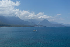 Sea and mountains with small touristic boat. KEMER, TURKEY - APRIL 25 View of sea and beautiful high mountains descending to sea with small touristic boat and Royalty Free Stock Photography