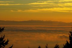 Sea and mountains with thick fog at sunset Royalty Free Stock Photos