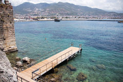 Sea and mountains view from Alanya castle. Sea and mountain view from Alanya castle with turquoise sea and rocks visible on bottom and pier Royalty Free Stock Photography