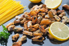 Sea Mussels. Steamed sea mussels, lemon, parsley and spaghetti royalty free stock photo