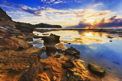 Sea Narrab Cliff Puddle Sky refl. Reflection of clouds and rising sun in still salt water puddle during low tide sea bed opening near sandstone cliffs of royalty free stock photos
