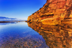 Sea Narrab Cliff Reflect Still. Warm illuminated hanging cliff of Narrabeen rocky headland at low tide with still shallow water reflect bright land and distant royalty free stock image