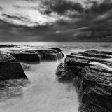 Sea Narrab Rocks square BW. Pacific ocean waves erosion of Australian coastline at Sydney Northern beaches. Crack in sandstone boulders under surf at sunrise in Royalty Free Stock Image