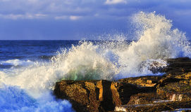 Sea Narrab Wave Rock. Strong rolling wave hits sandstone rocks of Pacific coast of Australia on a sunny morning against blue sky and open sea horizon Royalty Free Stock Photos
