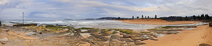 Sea Narrabeen Pool 2 beach panor. From rock pool to long clean Collaroy beach behind Narrabeen lake ocean entrance point in wide panorama at sunrise. Seascape of Stock Image