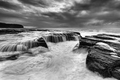 Sea Narrabeen 03 rocks BW. Dramatic rugged coastal seascape near Collaroy beach in Sydney at sunrise. Black-white image of surfing waves undermining rocks of Royalty Free Stock Photography