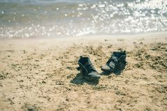 Sea is near. Shoes on the beach. The sea is glowing stock images