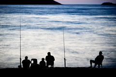 Sea/Ocean fishing. Fishermen sitting by the sea/ocean in darkness waiting for the catch Royalty Free Stock Photos