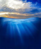 Sea or ocean underwater with sunset sky Royalty Free Stock Photo