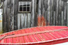 By the sea - Old weathered building behind the bottom of a red painted wooden boat with a rope stock photo