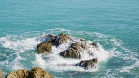 Sea smashing over some rocks stock photo