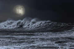 Sea in an overcast full moon night. Big white wave approaching the coast in an overcast full moon night royalty free stock photos