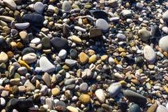 Sea pebble beach with multicoloured stones, waves with foam. Sea pebble beach with multicoloured stones, transparent waves with foam, on a warm summer day stock image