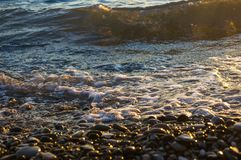 Sea pebble beach with multicoloured stones, waves with foam Royalty Free Stock Photography