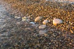 Sea pebble beach with multicoloured stones, waves with foam Stock Photos