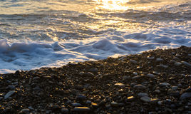 Sea pebble beach with multicoloured stones, waves with foam Stock Photography