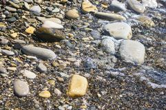 Sea pebble beach with multicoloured stones, waves with foam. Sea pebble beach with multicoloured stones, transparent waves with foam, on a warm summer day stock images