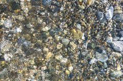 Sea pebble beach with multicoloured stones, waves with foam. Sea pebble beach with multicoloured stones, transparent waves with foam, on a warm summer day royalty free stock images