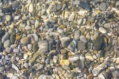 Sea pebble beach with multicoloured stones, waves with foam. Sea pebble beach with multicoloured stones, transparent waves with foam, on a warm summer day stock photos