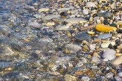 Sea pebble beach with multicoloured stones, waves with foam. Sea pebble beach with multicoloured stones, transparent waves with foam, on a warm summer day stock photo