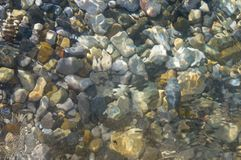 Sea pebble beach with multicoloured stones, waves with foam. Sea pebble beach with multicoloured stones, transparent waves with foam, on a warm summer day royalty free stock photos