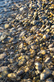 Sea pebble beach with multicoloured stones, waves with foam Royalty Free Stock Images