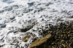 Sea pebble beach with multicoloured stones, waves with foam Royalty Free Stock Photo