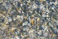sea pebble beach with multicoloured stones, waves with foam Stock Photo