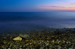 Sea and the pebble beach at sunset. Smooth sea, pebble beach and sunset sky Stock Images