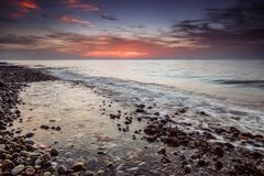 Sea pebble beach sunset Stock Images