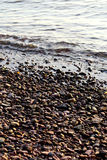 Sea pebble - gravel beach in sunlight, selective focus. Stock Images