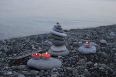 Sea pebble tower on the beach at sunset, with candles close up. Stock Images