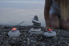 Sea pebble tower on the beach at sunset, with candles close up. Royalty Free Stock Photo