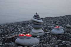 Sea pebble tower on the beach at sunset, with candles close up. Stock Photography