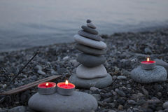 Sea pebble tower on the beach at sunset, with candles close up. Royalty Free Stock Photography