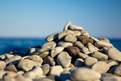 Sea pebbles on a beach in beams of the sunset sun Royalty Free Stock Photo